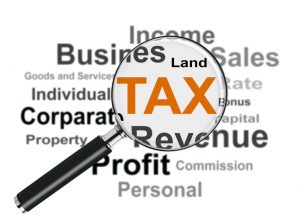 Magnifying glass higlighting the word tax