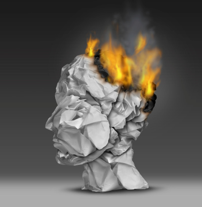 Image of a human head made of paper and the top is on fire.