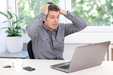 Foto de la persona que está muy estresada frente a una computadora portátil.