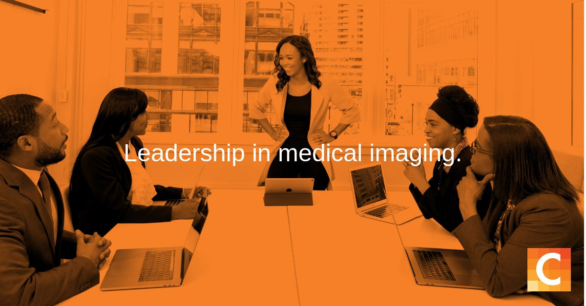 "In orange preset - 5 workers at table for meeting with leader standing at head of table - with text ""Leadership is Medical Imaging"""