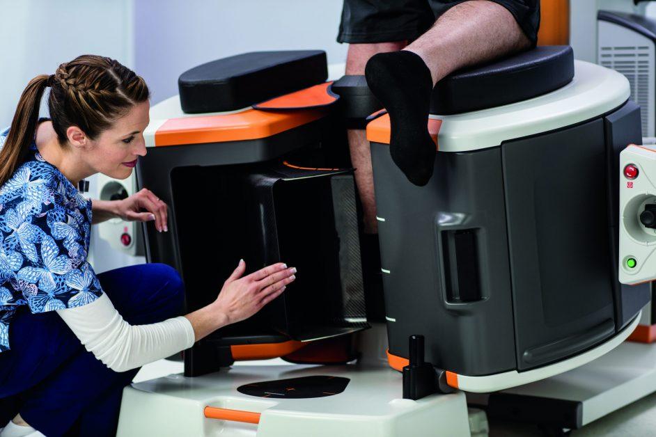 imagen de la enfermera que usa el sistema de extremidades OnSight de Carestream para capturar imágenes en el pie del paciente con carga de peso