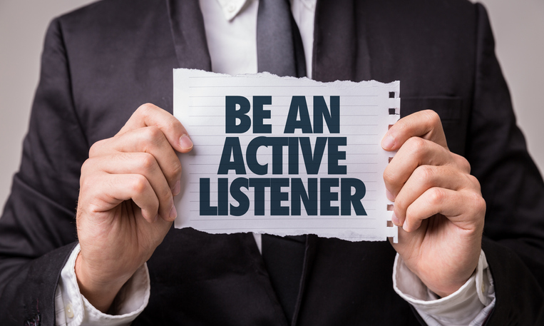 "Business person holding a sign -""Be an Active Listener"""
